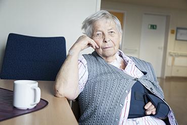 elderly woman in an arm sling